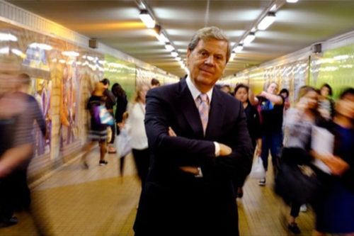 Ray Martin stands in a busy underpass, with other people out of focus along on either side.