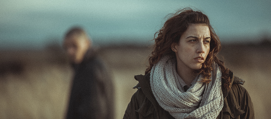 A woman in a field looking into the distance with a distraught expression. A man is standing in the background looking towards her, out of focus.