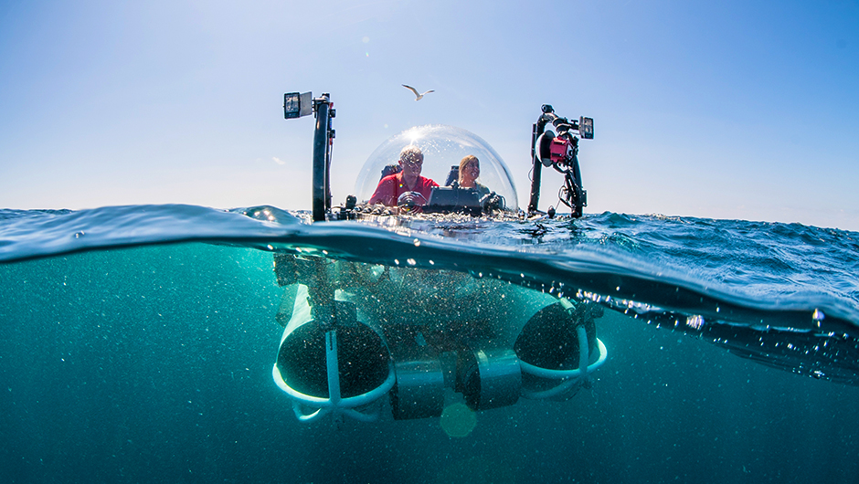 Two people in a mini-submarine in the ocean with underwater cameras attached to the outside.