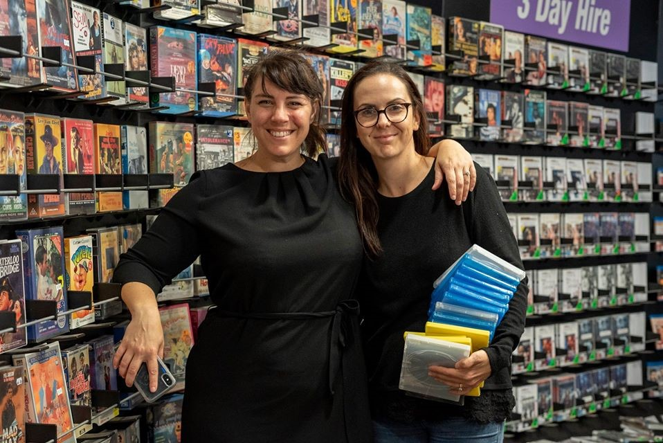 Two people standing in a video store in front of a wall of DVDs
