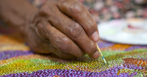 Close up photo of a hand holding a paintbrush creating a dot painting