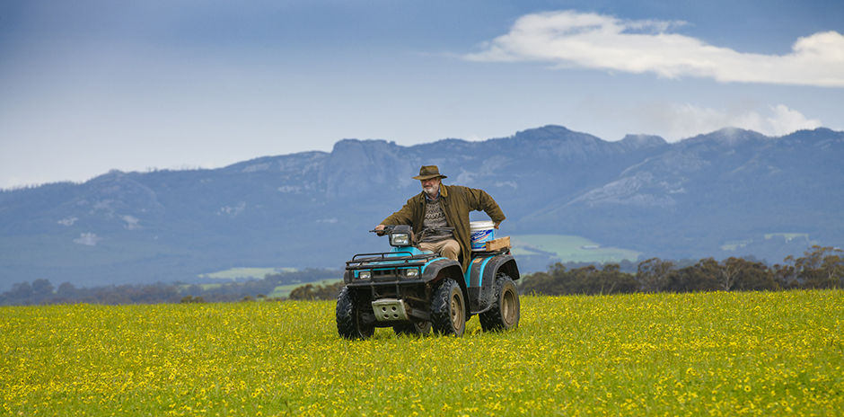 Sam Neil driving a quadbike in a field with hills in the background