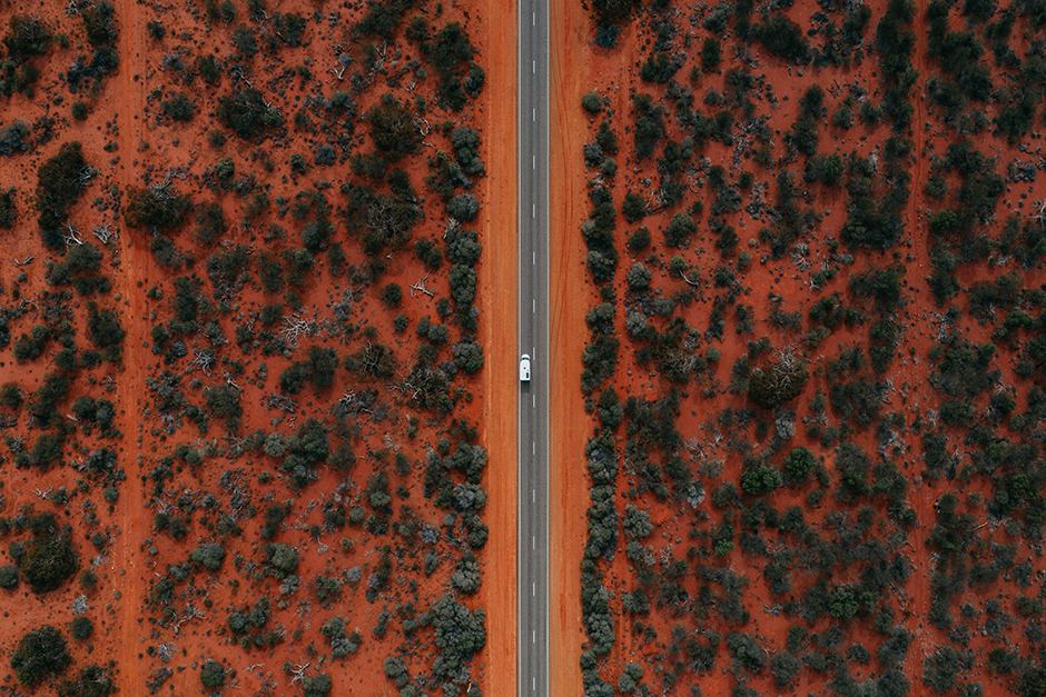 Aerial photo of long straight road surrounded by red earth and bushland in the Shark Bay World Heritage Area