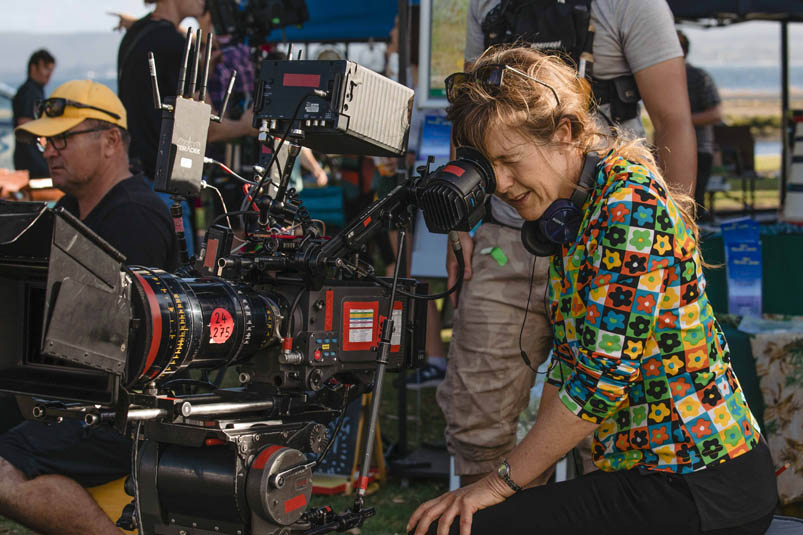 Director Renee Webster on set with a professional film camera.