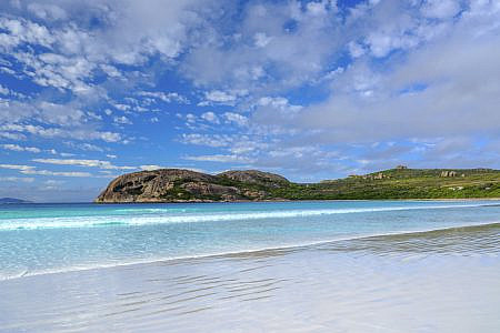 Calm beach with clear blue skies and grassy coast in the background