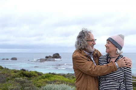Moira and Leon Pericles smiling and looking lovingly at each other on Redgate Beach