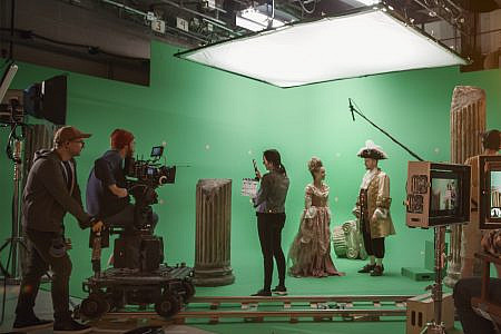 Behind the scenes of big film production in a studio with lighting, cameras, green screen and film crew.