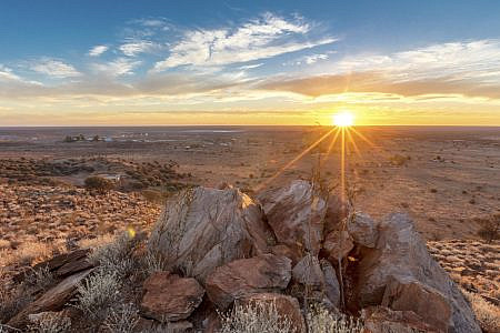 Outback with red earth, scrubland and rocks with sun hanging low over the horizon in a clear blue sky.