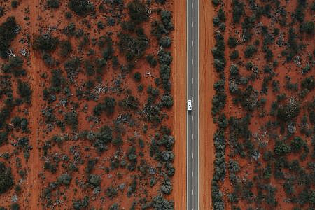 Aerial photos of white vehicle driving down a road surrounded by red earth and scrubland.