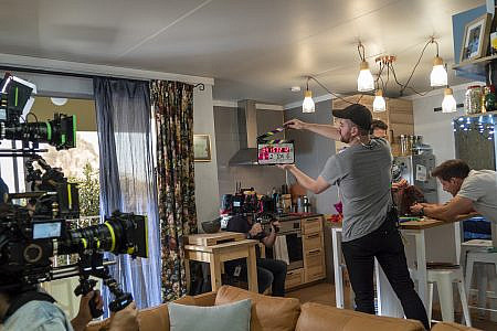 Behind the scenes of an appartment TV set with film cameras and crew