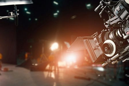Close up of video camera in a film studio with crew out of focus in the background