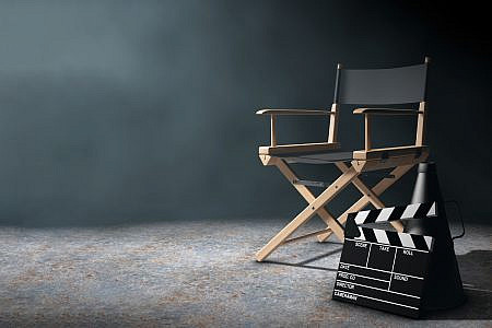 Director chair, film clapper and a megaphone on a dark stage