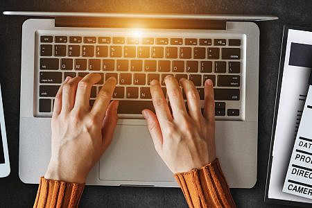 Hands typing on a laptop with a film clapper, tablet and clipboard