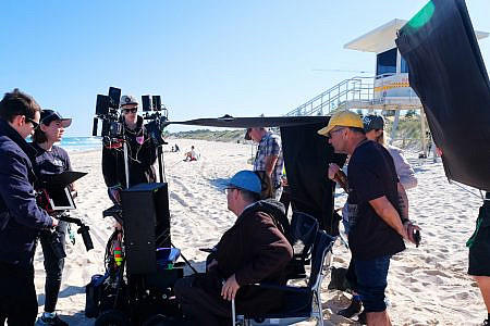 Film crew watching a shot on a monitor on the beach