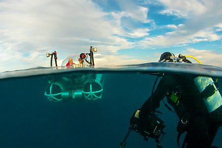 Odyssea submarine descending below the ocean surface with a camera operator in a scuba suit in the foreground