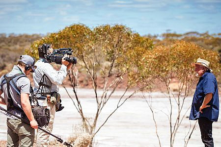 Two crew members with camera and sound equipment filming 'Dust Devils' Mike Armstrong in the outback