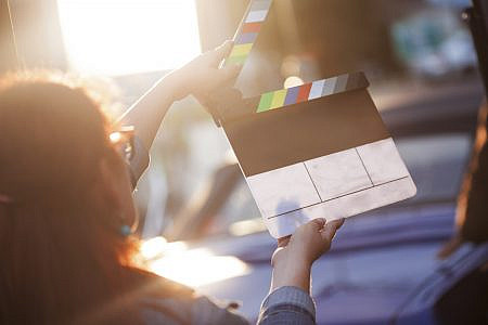 Person holding a clapperboard in front of the camera, the filming process.