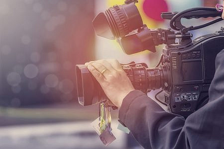 Close up of someone operating a film camera