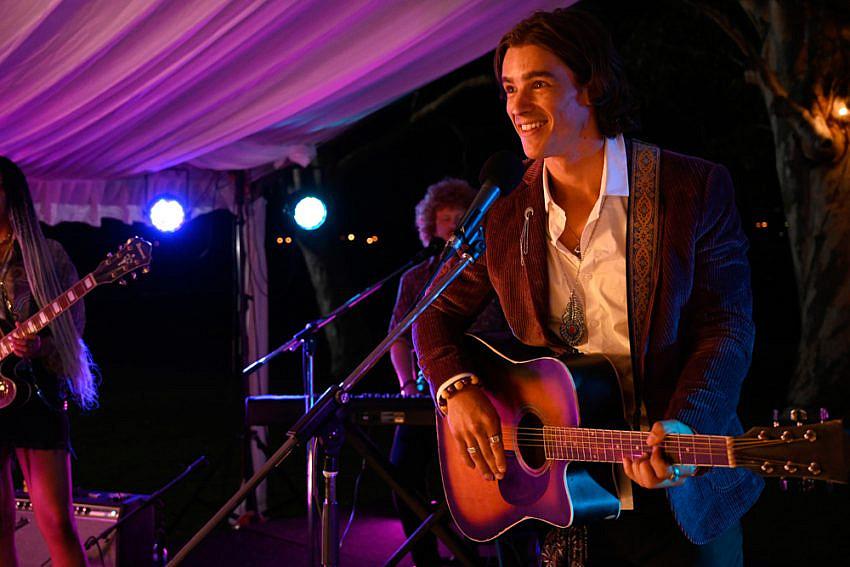 Brenton Thwaites (as Devon) on a stage with a guitar