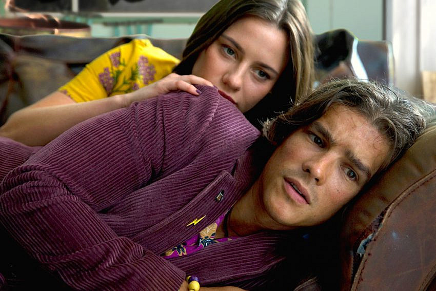 Brenton Thwaites as 'Devon' and Lily Sullivan as 'Lucy' on a couch in I Met A Girl