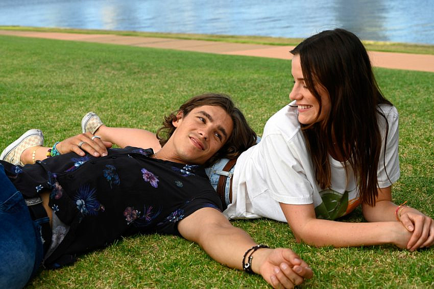 Lily Sullivan (as Lucy) & Brenton Thwaites (as Devon) lying on grass by the river.