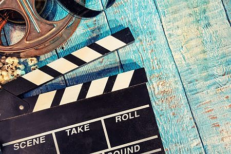 Close up of a film clapper, film reel and popcorn against a wooden background