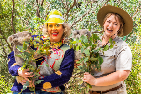 Andrea Gibbs in a yellow visor and Bonnie Davies in a ranger Stacey-esque costume both smiling and holding Koalas in front of thick scrub.