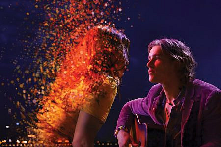 Brenton Thwaites (as Devon) with a guitar looking at Lily Sullivan (as Lucy) as she dissolves into stars and lights