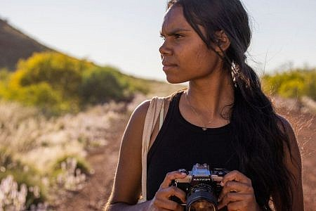 Murra stands on a red dirt road holding an old DLSR camera. She has her hair in a low ponytail and a calico bag on her shoulder.