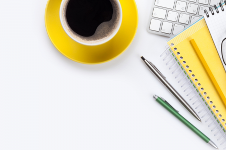 White desk with a yellow cup and saucer filled with black coffee next to a keyboard, yellow notebook, reading glasses and pens in the top right-hand corner.